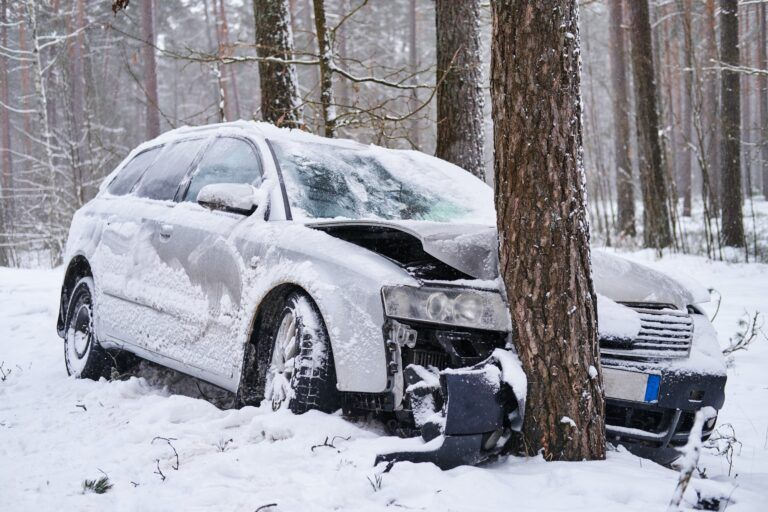 Broken car crashes into tree after losing control on slippery road in snowy forest.